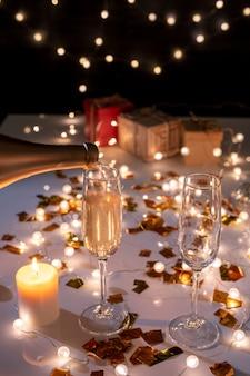 Duas flautas e uma vela acesa na mesa entre confetes dourados e guirlandas acesas preparadas para a celebração do natal