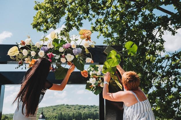 Duas floristas femininas trabalhando em um arco de casamento incomum preto com carcaça sólida