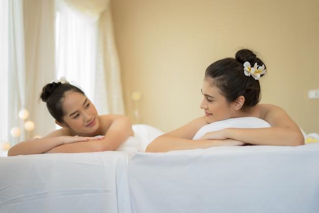 Duas fofinhas jovens durante um tratamento de cuidados com a pele em um spa.