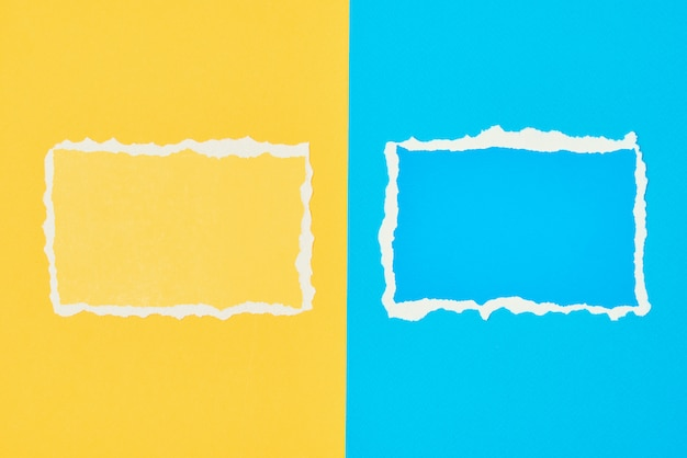 Duas folhas de borda rasgadas de papel rasgado no fundo azul e amarelo