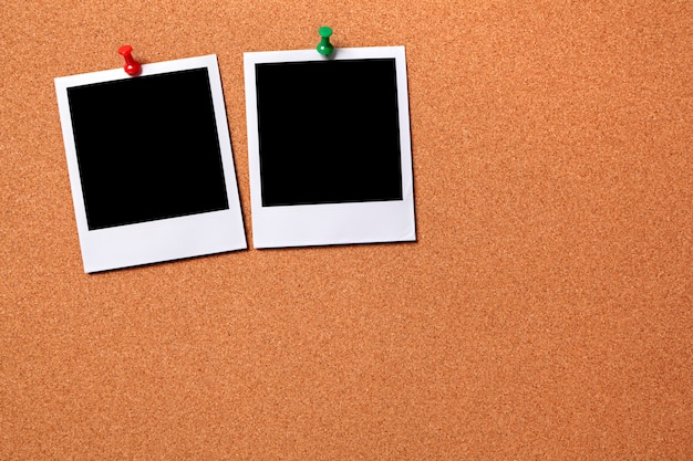 Duas fotos polaroid impressões em uma placa de observação da cortiça