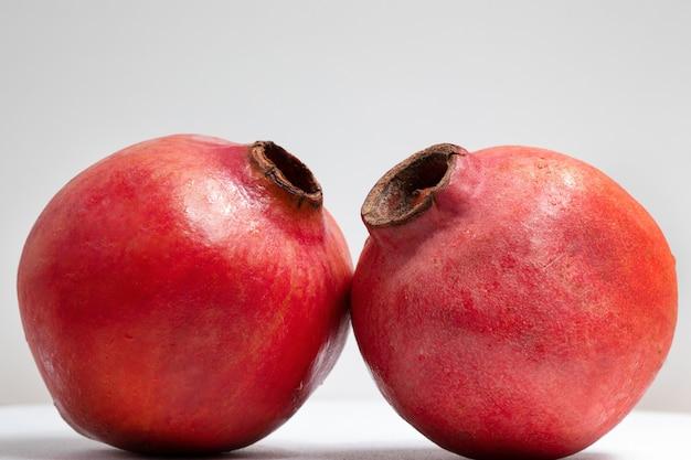 Duas frutas da romã isoladas em um fundo branco.
