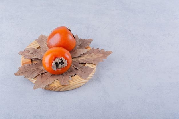 Duas frutas frescas de caqui e folhas secas na placa de madeira.