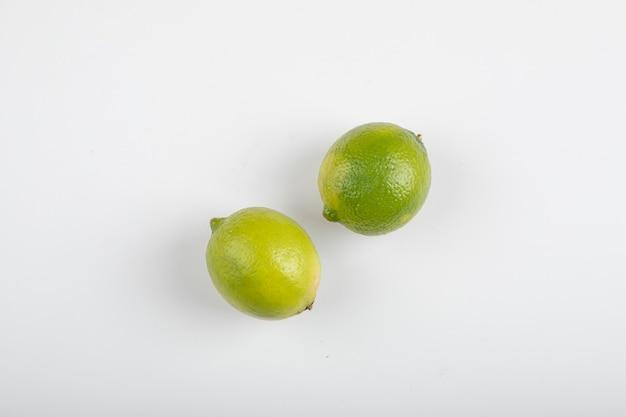 Duas frutas maduras de limão isoladas na mesa branca.