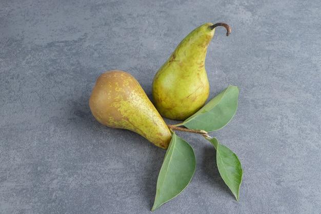 Duas frutas maduras de pêra vermelha amarela isoladas em uma superfície cinza