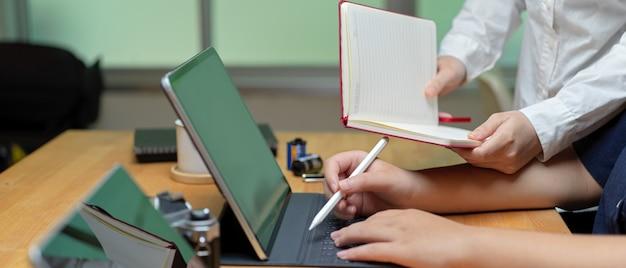 Duas funcionárias, briefing sobre seu projeto com tablet e caderno em branco