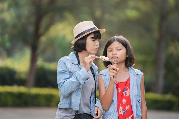 Duas garota tomando sorvete na rua durante uma caminhada no parque