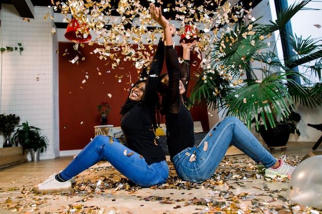 Duas garotas africanas, felizes amigos elegantes comemorando o ano novo ou festa de aniversário sentar um com o outro e jogar um confete. moda elegância mulheres aproveitando o tempo juntos.
