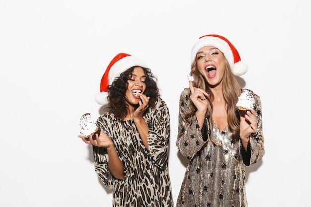 Duas garotas alegres bem vestidas com chapéus vermelhos comemorando o ano novo isoladas no espaço em branco