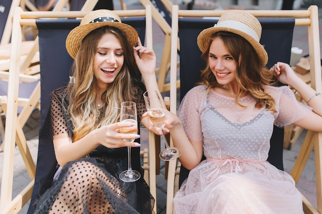 Duas garotas alegres com os mesmos chapéus de palha comemorando o feriado com champanhe em poltronas reclináveis