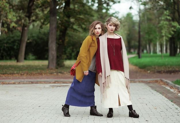 Duas garotas alegres no parque outono