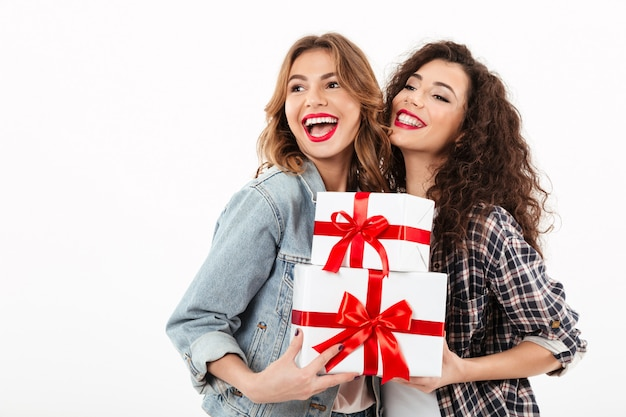 Duas garotas alegres posando com presentes e olhando para longe sobre parede branca