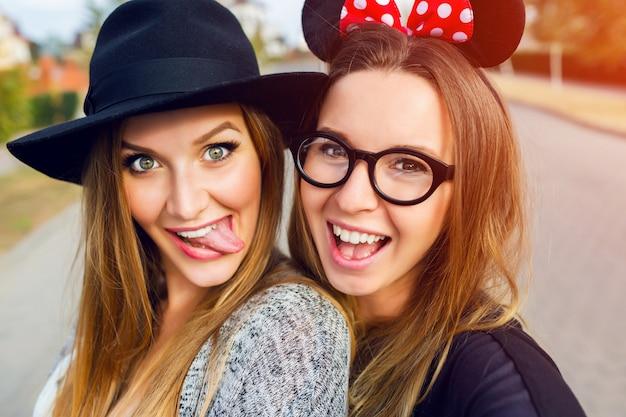 Duas garotas alegres se divertindo na rua.