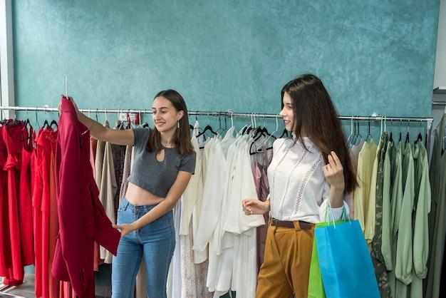 Duas garotas amigáveis passando um tempo para fazer compras na loja de moda. estilo de vida