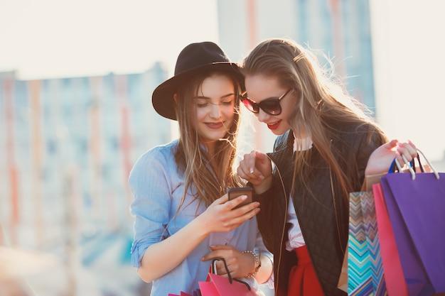 Duas garotas andando com as compras nas ruas da cidade