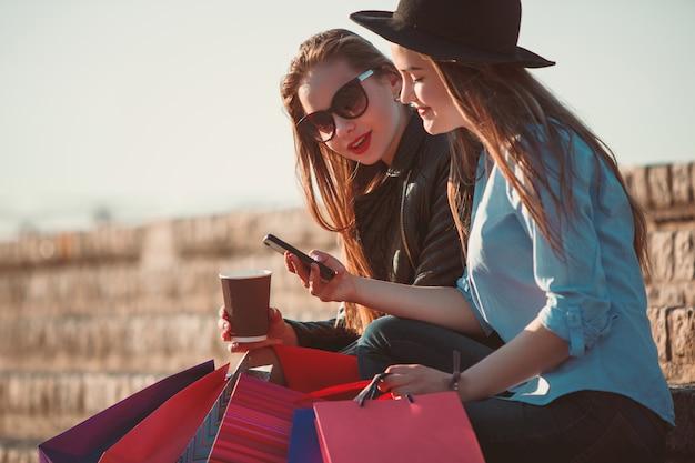 Duas garotas andando com sacolas de compras nas ruas da cidade em dia de sol