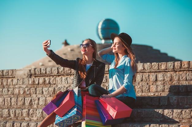 Duas garotas andando com sacolas de compras nas ruas da cidade em um dia ensolarado