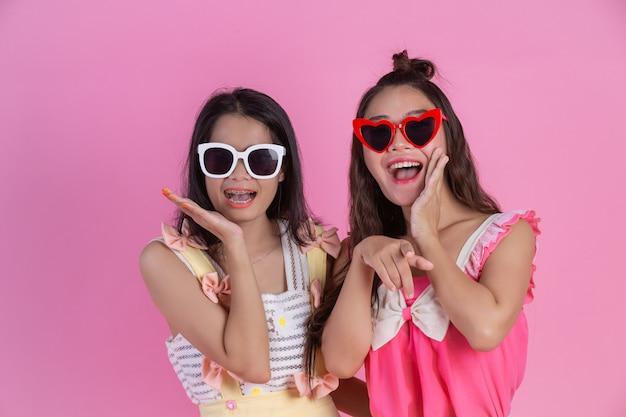 Duas garotas asiáticas amigas são felizes e têm um rosa.