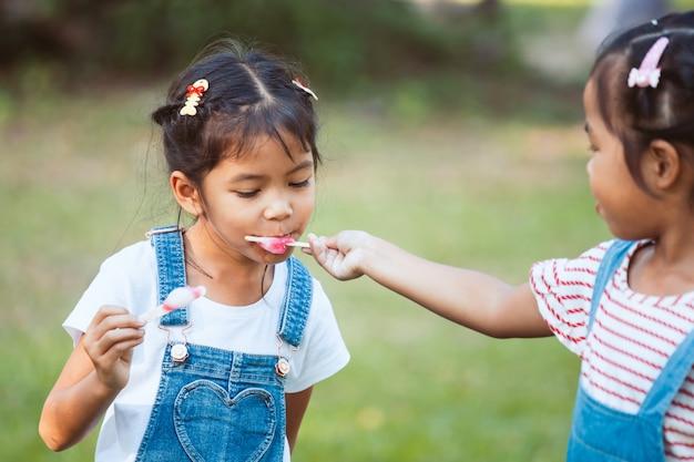 Duas garotas asiáticas bonito criança comendo sorvete juntos no parque