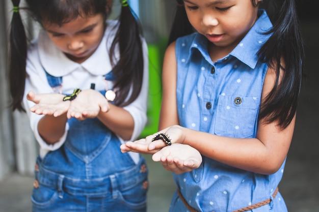 Duas garotas asiáticas bonito criança segurando e brincando com lagarta preta