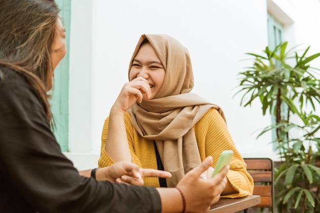 Duas garotas asiáticas conversando e segurando um telefone celular