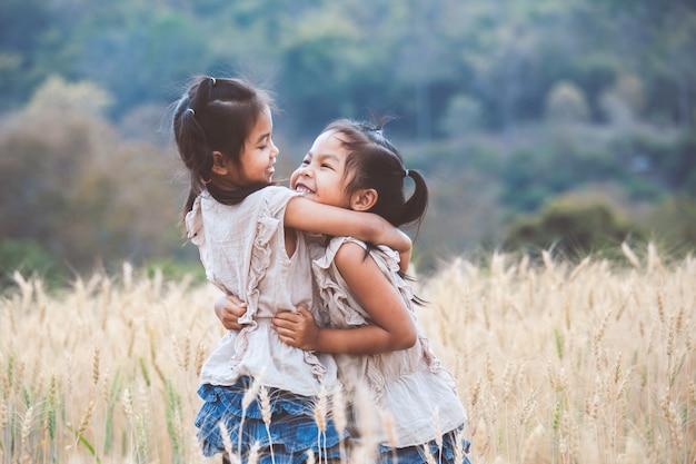 Duas garotas asiáticas criança abraçando uns aos outros com amor e jogando juntos no campo de cevada