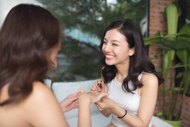 Duas garotas asiáticas pintando as unhas dos pés e das mãos em uma cama na sala de estar