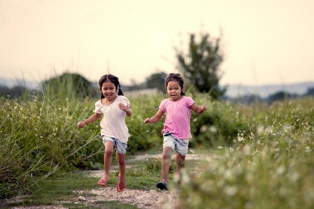 Duas garotas asiáticas se divertindo e correndo juntos no parque em tom de cor vintage