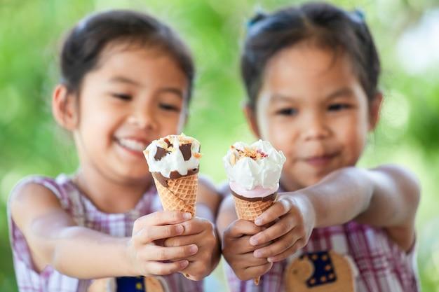 Duas garotas asiáticas segurando delicioso sorvete waffle cone juntos na mão
