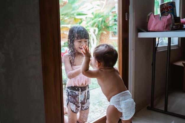 Duas garotas asiáticas sorrindo uma para a outra através do vidro da janela