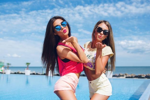 Duas garotas atraentes com cabelo comprido estão se passando perto da piscina no sol. eles estão mandando um beijo para a câmera.