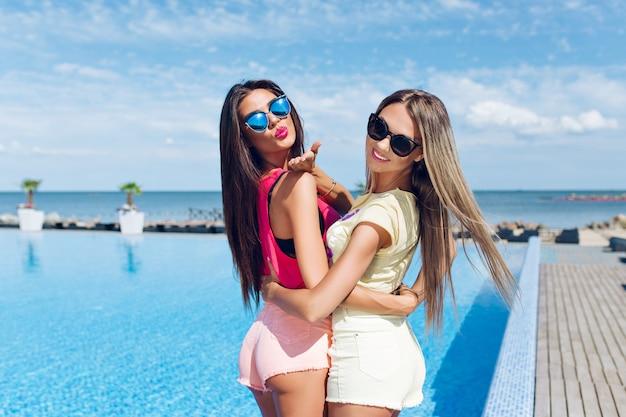 Duas garotas atraentes em óculos de sol com cabelo comprido perto da piscina no sol. vista de trás.