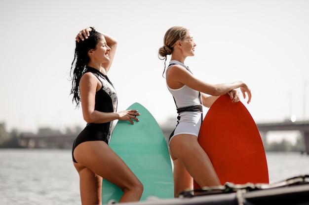Duas garotas atraentes em pé com wakeboards no lago
