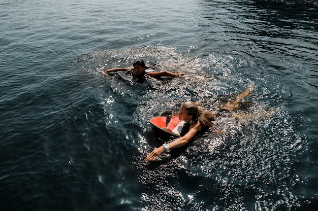 Duas garotas atraentes nadando no wakeboard no lago