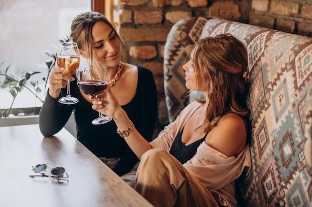 Duas garotas atraentes sentadas em um café bebendo vinho