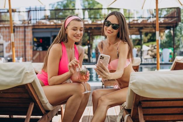 Duas garotas atraentes tomando coquetéis à beira da piscina