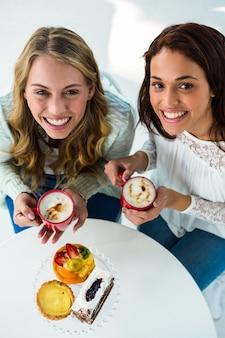 Duas garotas bebem café e comer doces