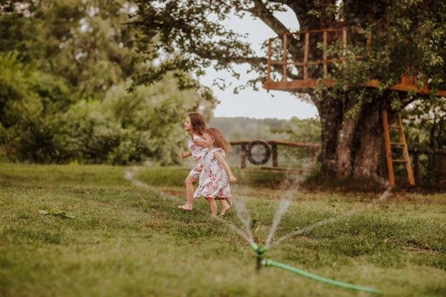 Duas garotas bonitas brincando com salpicos de água na clareira verde