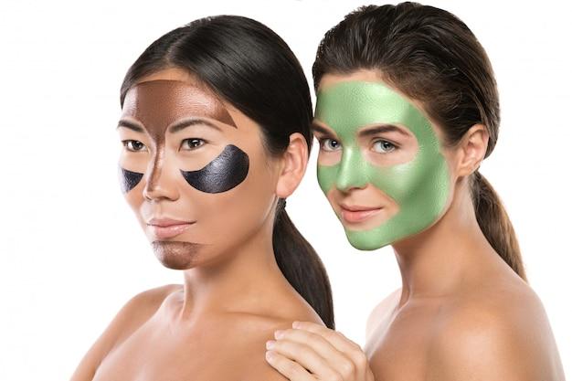 Duas garotas bonitas com máscaras coloridas destacáveis em seus rostos