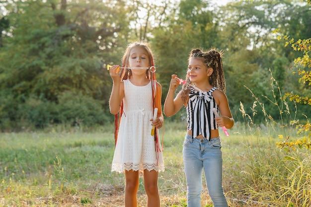 Duas garotas bonitas com rabo de cavalo estão brincando no parque, explodindo bolhas de sabão.