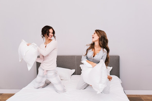 Duas garotas bonitas de pijama, tendo a luta de almofadas na cama.