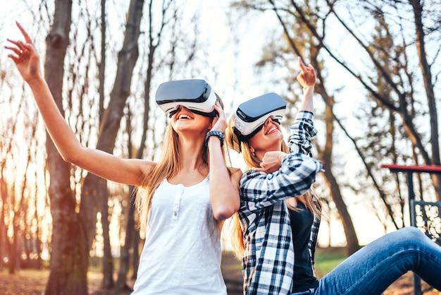 Duas garotas bonitas desfrutar de óculos de realidade virtual ao ar livre