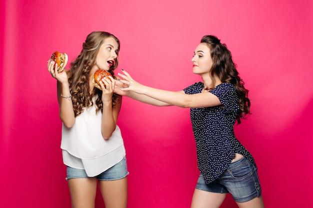 Duas garotas bonitas e famintas querendo dois hambúrgueres grandes.