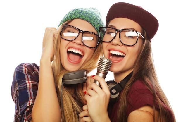 Duas garotas bonitas e hipster com um microfone cantando e se divertindo