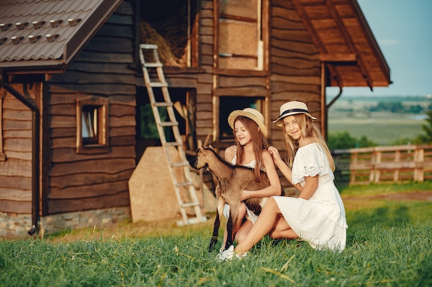 Duas garotas bonitas em um campo com uma cabras