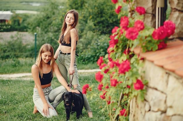 Duas garotas bonitas em um parque de verão com um cachorro