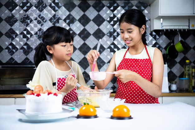 Duas garotas bonitas fazendo bolo