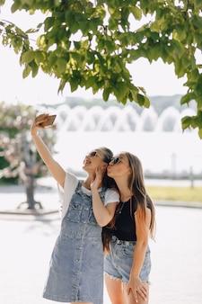 Duas garotas bonitas passeando no parque tirando fotos de si mesmas ao telefone