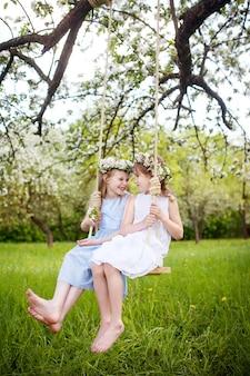Duas garotas bonitas se divertindo em um balanço no florescimento antigo jardim de macieira. dia ensolarado. atividades ao ar livre de primavera para crianças