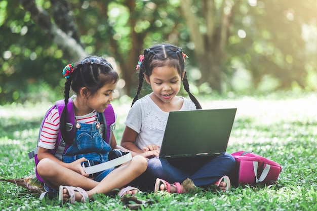 Duas garotas bonito criança asiática usando laptop no parque juntamente com diversão e felicidade